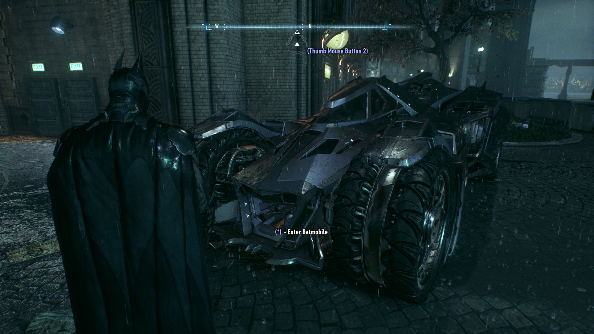 Batman standing besides the Batmobile